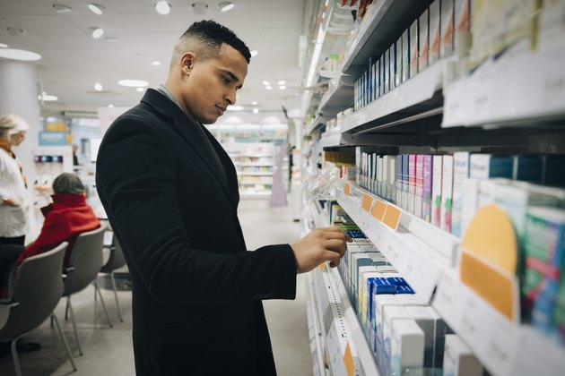 Side view of male customer choosing medicine from rack at pharmacy store