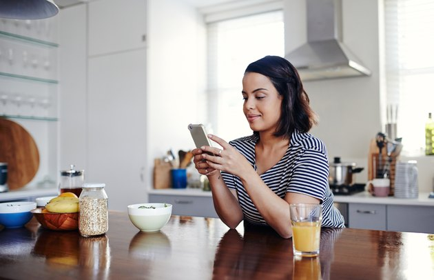 Woman on phone tracking net carbs in the kitchen surrounded by orange juice and oatmeal