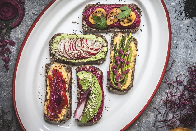 Multicoloured hummus on toasts Vertical