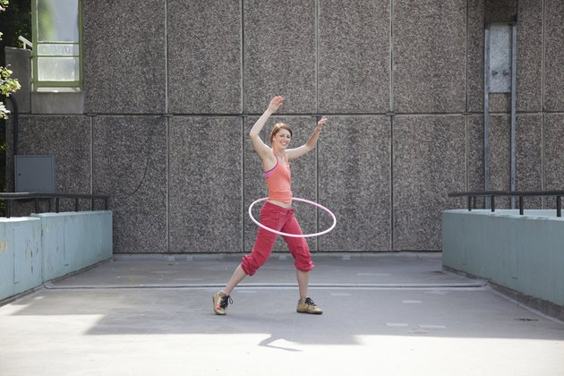 Woman hula hooping on city street