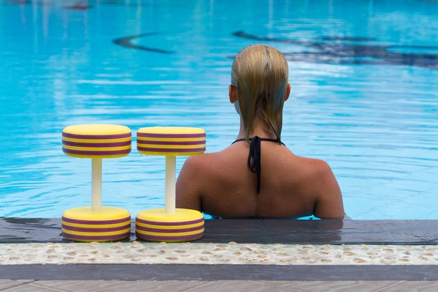 Woman is engaged aqua aerobics with dumbbells