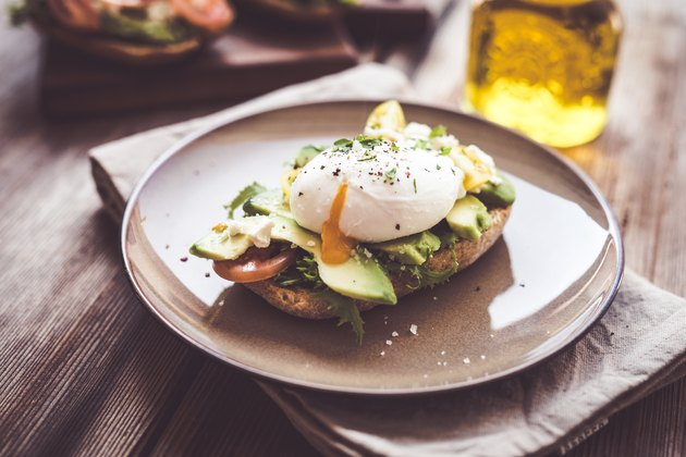 A sandwich with avocado and poached egg