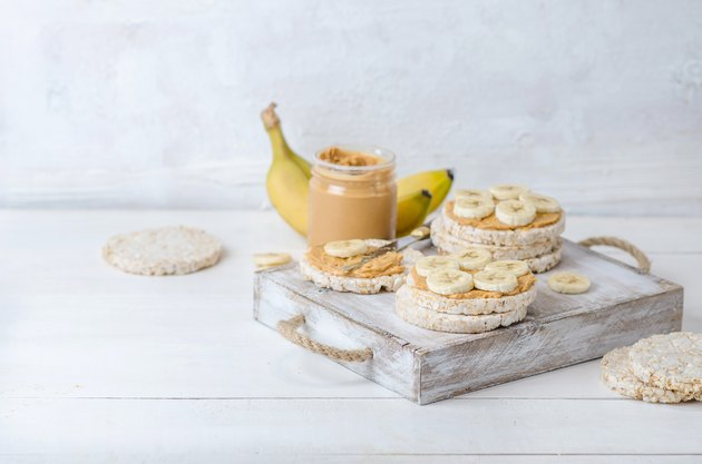 Healthy breakfast with rice cakes with peanut butter and slices of banana on white wooden table. Space for text.