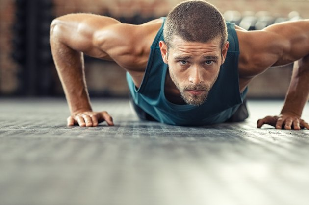 Determined man doing push ups at the gym