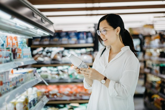 Young Asian woman grocery shopping in supermarket and holding a bottle of fresh milk