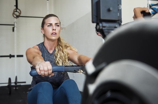 Focused athlete exercising on rowing machine in crossfit gym