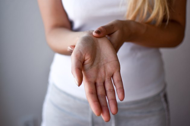 Closeup woman holds her wrist hand injury, feeling pain. Health care and medical concept