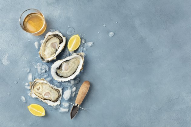 Fresh raw oysters, shot from above on ice with a glass of white wine, lemon slices, shucking knife and copy space