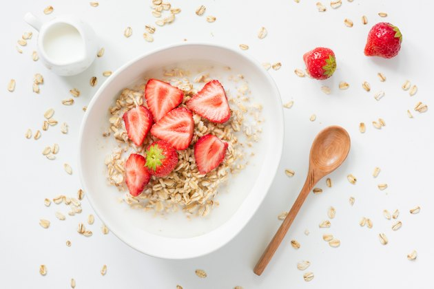 Oatmeal porridge with strawberries and milk in bowl