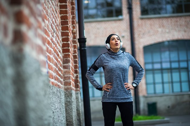 Young athlete woman taking a break from her run with symptoms of low blood sugar after exercise