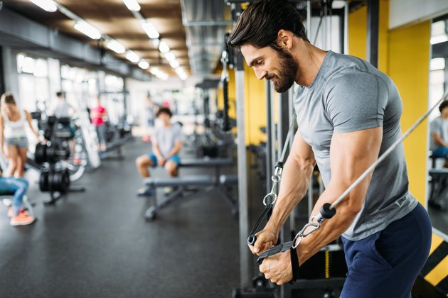 Man using the cable machine at the gym to work his chest during a full-body workout