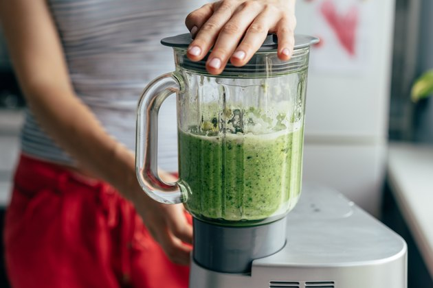 Close view of a woman on the Body Reset Diet blending a green smoothie
