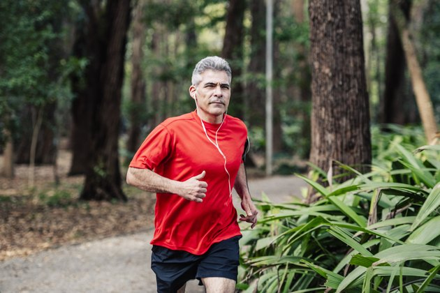 Mature man jogging in woods with earphones