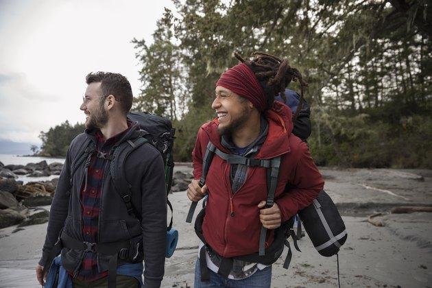 Friends backpacking on rugged beach