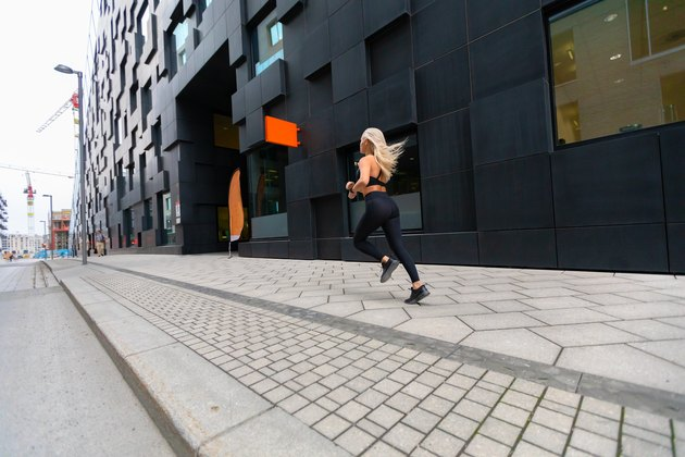 Back view of a fast running fit woman in modern city environment