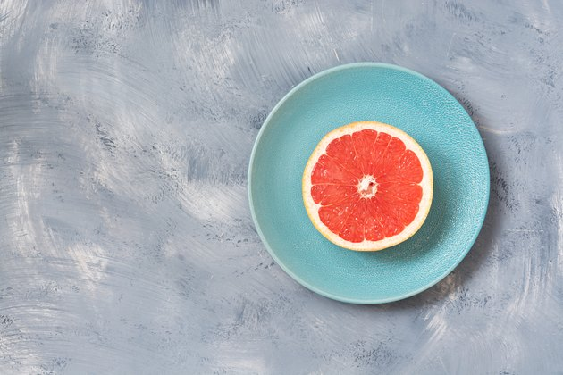 Half of the grapefruit is a blue plate, gray background. Copy space.