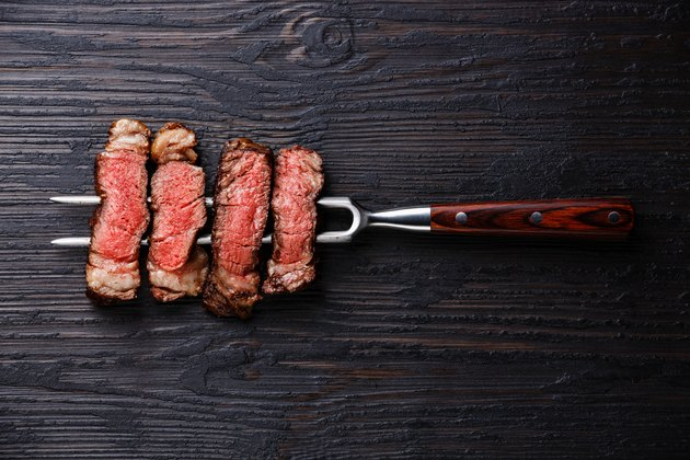 Slices of grilled meat barbecue steak Rib eye on meat fork