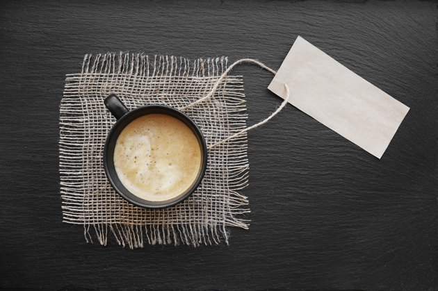 Coffee in black cup on rustic burlap and label blank paper card. Top view with copyspace for your text. black background, cappuccino, price tag