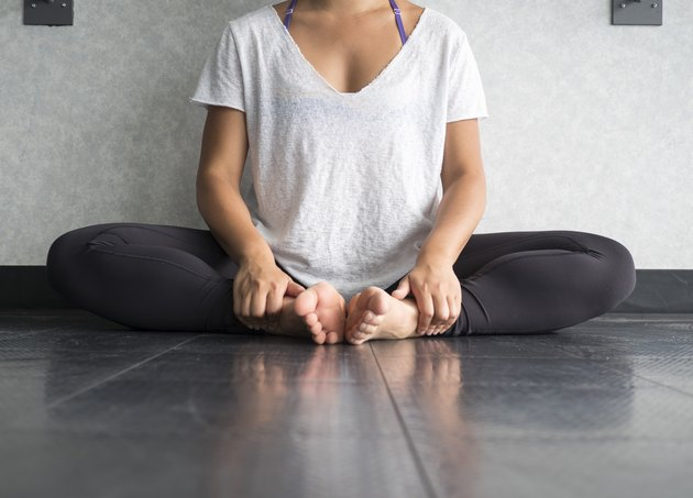 Female dancer sitting down in butterfly pose doing yoga
