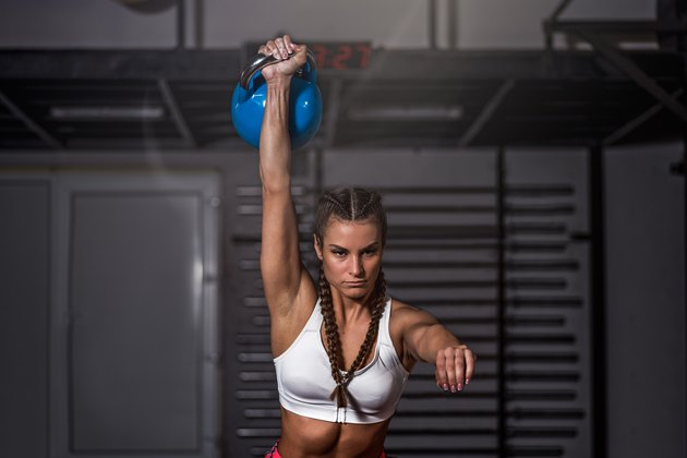 woman holding a heavy kettlebell with one hand in Turkish get-up