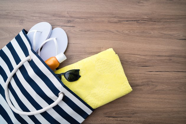 white flip flops yellow towel and black sunglasses on wooden floor coming out of striped beach bag