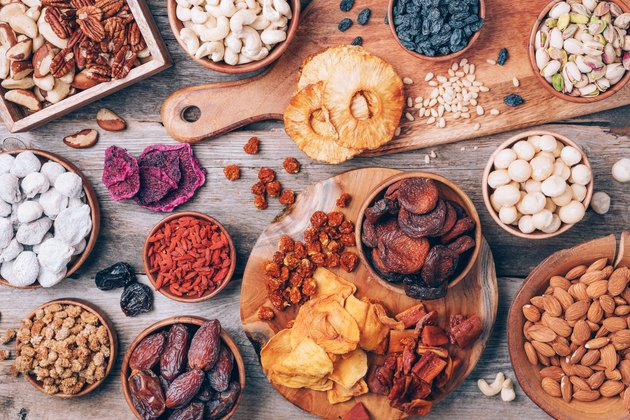 Mix of dried fruits and nuts -brazil nuts, cashew, pecan, almonds, macadamia, pine nuts, hazelnuts, pineapple, raisins, dates, dried apricots, goji, papaya, figs, mulberry on wooden background.Top view. Superfood, vegan, vegetarian concept