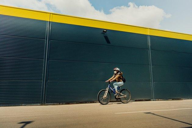 妇女戴头盔,面罩和背包骑自行车上班