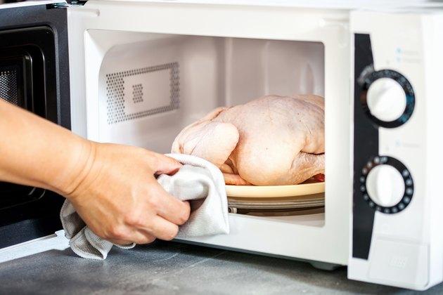 手将生鸡肉在微波炉
