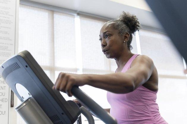 Mature woman exercising on elliptical machine