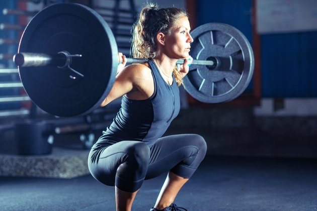 Female Athlete Exercising With Barbell In Gym