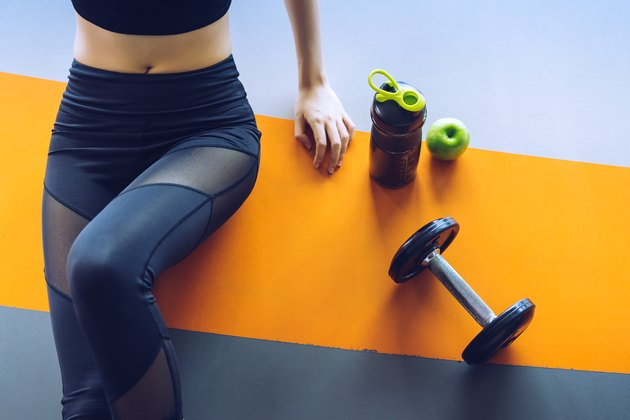 Midsection Of Woman Sitting By Water Bottle And Dumbbell