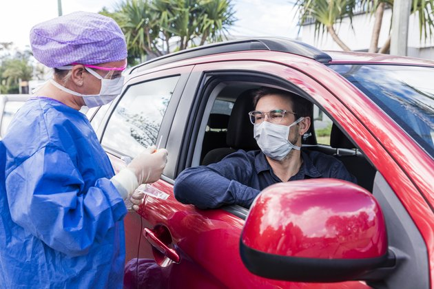 A doctor taking a nasal swab from a driver in a red car
