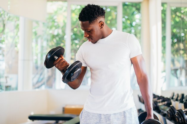 Young African American man doing biceps curls