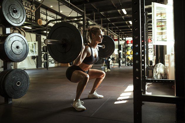Woman squatting with a barbell.