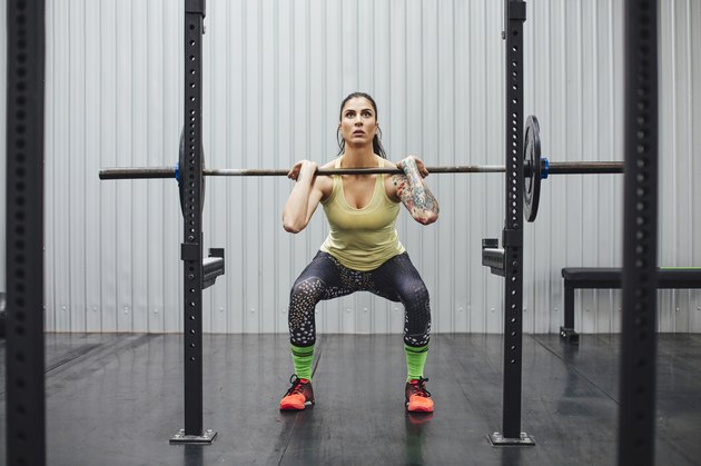 Confident woman lifting deadlift in gym