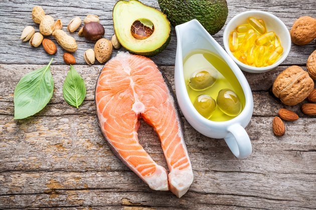 Selection food sources of vitamin b and unsaturated fats. Superfood high vitamin e and dietary fiber for healthy food. Almond,pecan,hazelnuts,walnuts,olive oil,fish oil and salmon on wooden background.