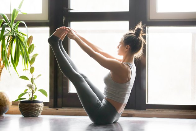 Young attractive woman in Paripurna Navasana pose, home interior