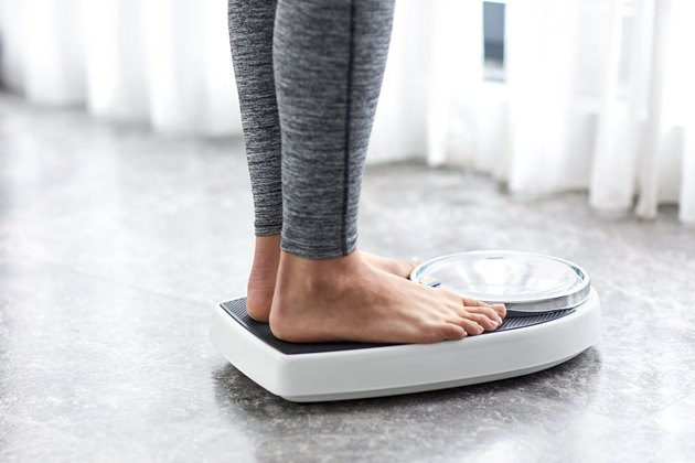 Woman on a low-carb diet weighing herself on a home scale
