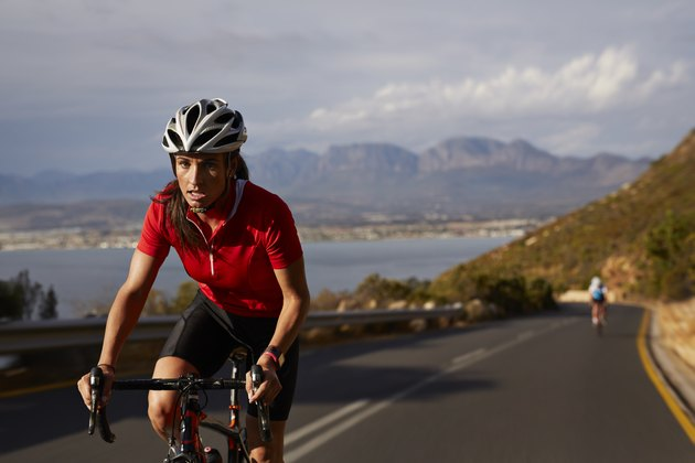 Female pro cyclist taking lead on mountain climb
