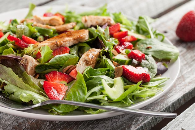 Side view of a leafy green salad with strawberries and grilled chicken