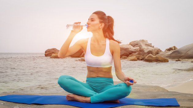 Fitness woman drink water after doing sport exercises on beach at sunset