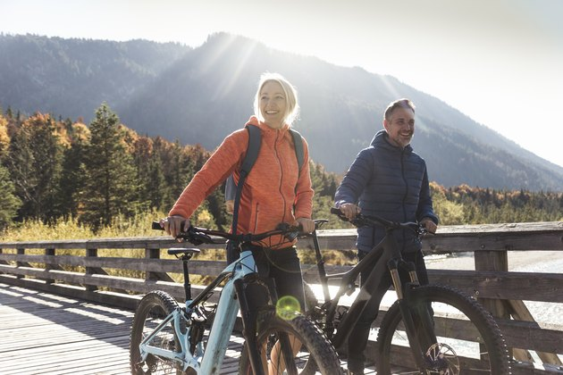 Couple with mountain bikes crossing a bridge, getting their daily recommended amount of cardio