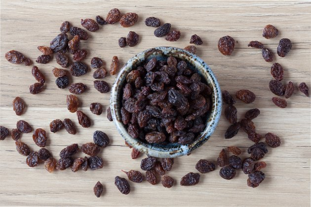 Organic raisins in bowl on wood