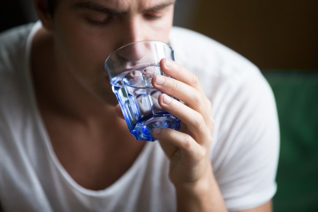 Young man feeling thirsty dehydrated holding glass drinking water, closeup