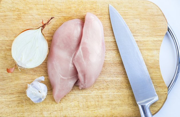 Top View of Raw Chicken Breasts, Fillets on a Wooden Cutting Board with Ingredients, Chopped Half Onion, Whole Garlic Bulb, and Stainless Chef Knife. Organic Food, Poultry Meat Cooking Concept
