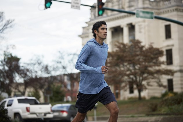 Young Latino man in blue sweatshirt runs by small town courthouse