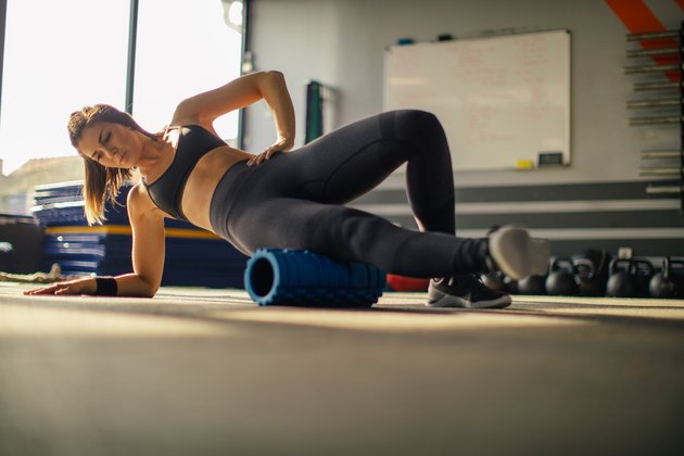 Young woman foam rolling muscle knots at the gym