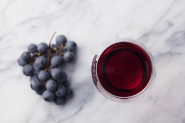 Red wine in glass with fresh grape on marble table background. Top view.