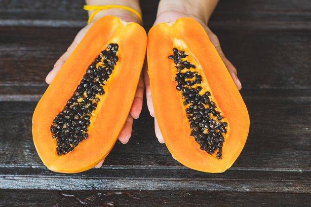 Cropped Hand Of Woman Holding Halved Papayas