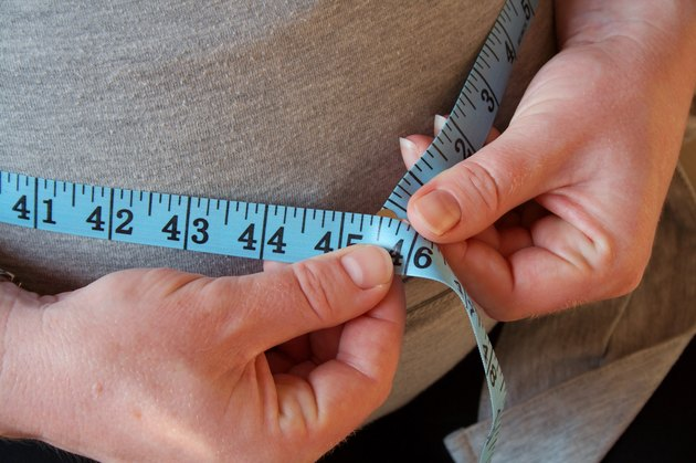 Close view of a woman using a measuring tape to measure her belly fat